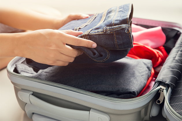 Close up of a woman packing clothes into travel bag