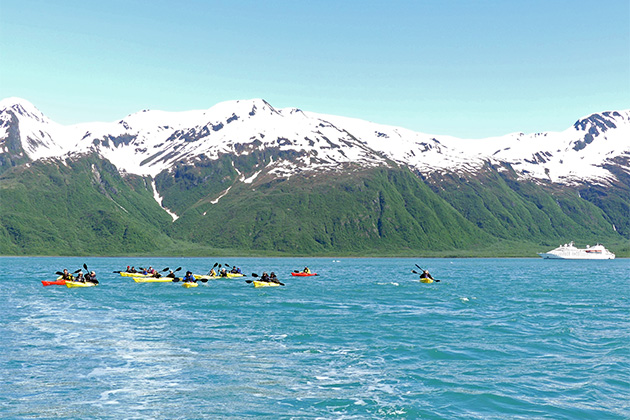 Passengers kayaking in Alaska, with mountains and Windstar ship in the background
