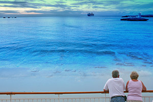 A senior couple look out over the beach toward their cruise ship