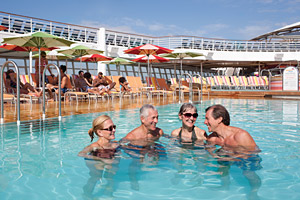 An older and younger couple swim together in a cruise ship pool
