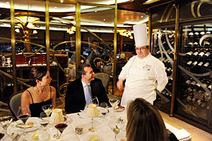 Chef Arnaud Lallement Speaking to Three Diners at a Table in a Fancy Restaurant