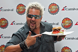 Chef Guy Fieri Holding a Plate With a Fieri Burger On It