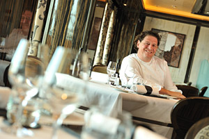 Chef Jacques Marco Pierre White Sitting at a Table in an Empty Restaurant Smiling at the Camera