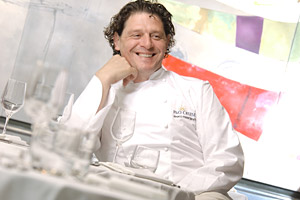 Chef Marco Pierre White Sitting at a Table Smiling