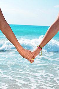 olivia-cruise-lesbian-beach-holding-hands