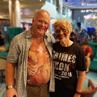 Older couple in zombie makeup smiling on cruise ship