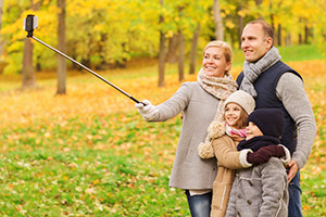 family taking selfie with smartphone and monopod