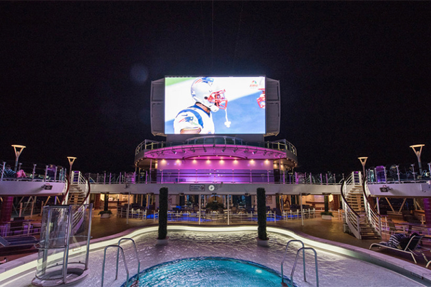 Outdoor movie screen overlooking pool on a cruise ship at night