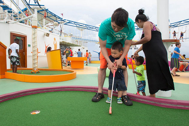 Man and his son playing mini-golf on Carnival Breeze.