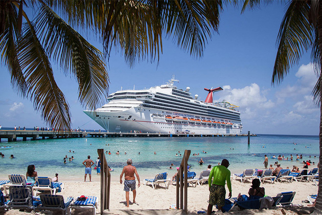 Cruise ship docked at beach with people and palm trees