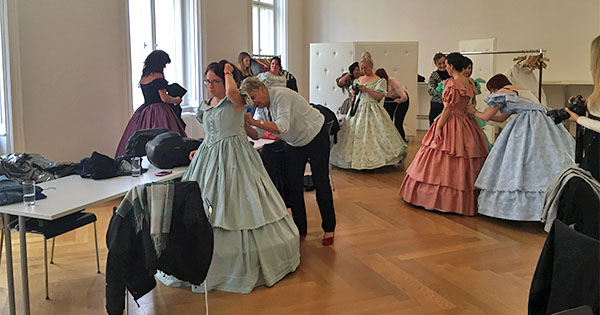 Women changing into hoop skirts and 18th-century dresses