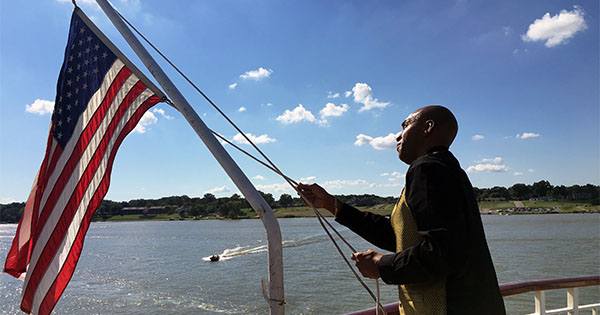 crew member hoisting the flag