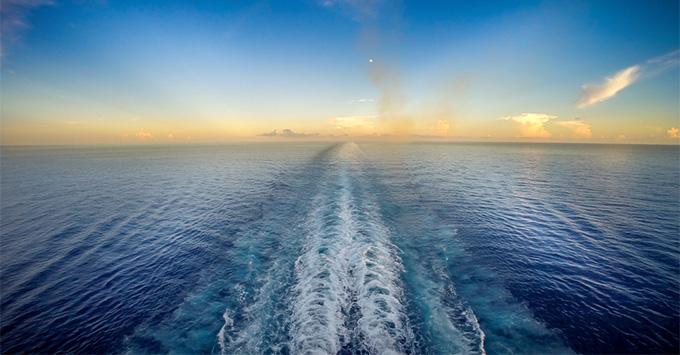 Shot of blue cruise wake following behind a cruise ship at sea during sunset