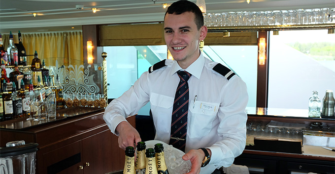 Smiling ms Emerald crew members serving Moet Champagne