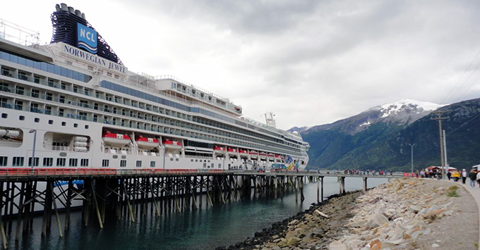 Norwegian Jewel in port, with mountain landscape in the background