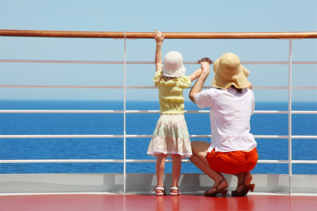 behind mother and her daughter standing on deck of yacht and they look far aboard