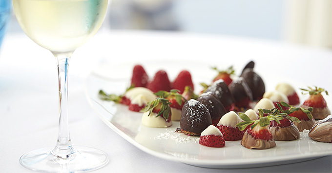 Chocolcate covered strawberries on a plate with white wine