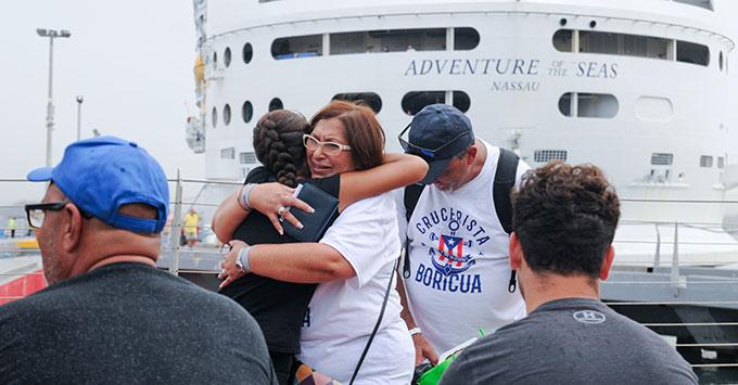 Evacuees hug next to cruise ship