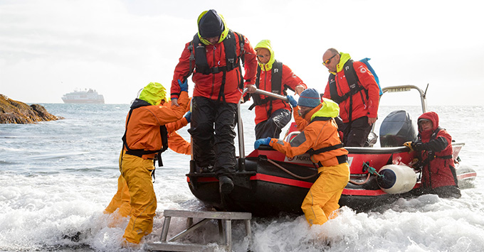 Fram's Expedition Team helping passengers off a tender boat in Greenland