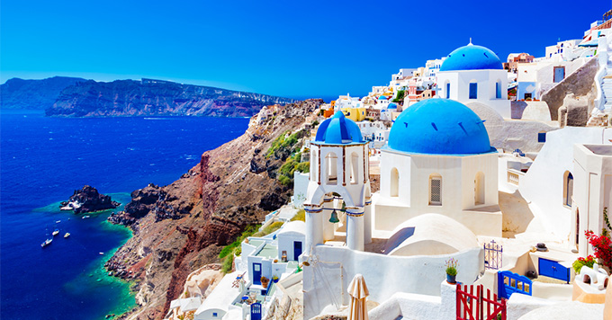 Traditional and famous houses and churches with blue domes over the Caldera, Aegean sea in Santorini