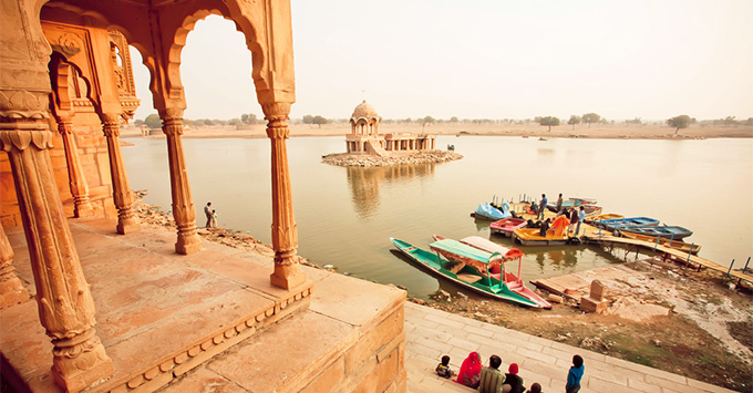 Colorful boats on indian river and group of tourists having rest near water on February 2, 2015. Every winter Jaisalmer takes famous Desert Festival of Rajasthan