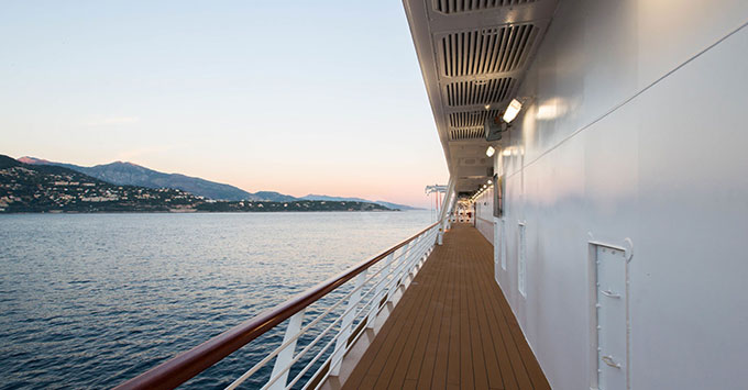 Cruise ship outdoor deck at sunset with mountains in the background