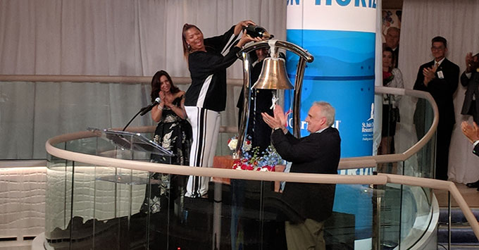 Queen Latifah, godmother of Carnival Horizon, pouring champagne over the ceremonial bell in Carnival Horizon's atrium, christening the new ship.