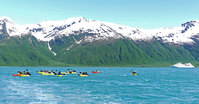 Passengers kayaking with Alaska scenery in the background
