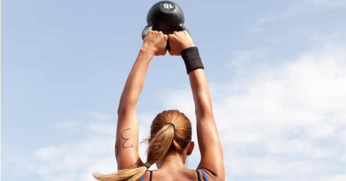 Young woman doing kettlebell swings at crossfit competition