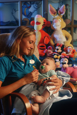 A Disney youth crewmember rocks an infant to sleep