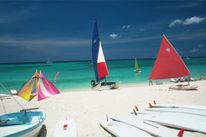 sailboats and surf boards on the beach in Grand Cayman