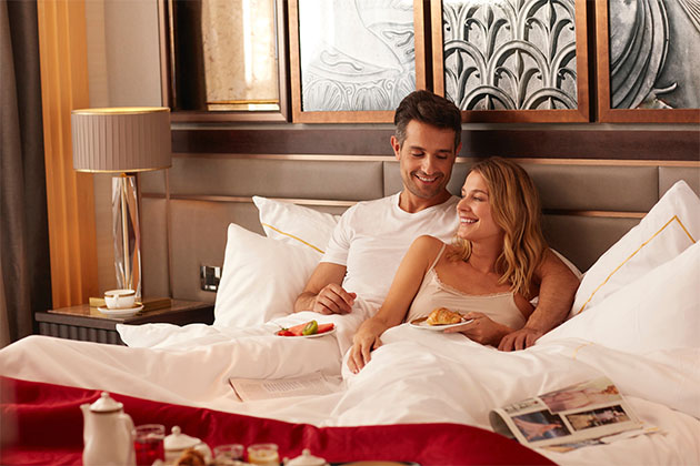 Couple enjoying a restful morning in their suite on Queen Mary 2 (Photo: Cunard)